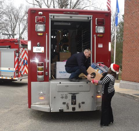 Terry Creighton of O&G hands a box of toys to Robert Shopey III of the Torrington Fire Department in front of O&G's Torrington headquarters.
