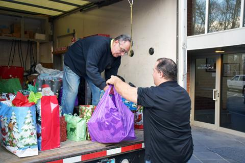 O&G's Mark Zavatkay hands bags of toys to O&G driver Lenny Byram as they load the truck in preparation for a toy delivery to the Torrington Area Youth Service Bureau.