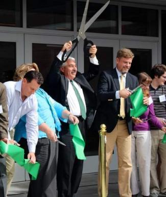 Principal Rick Misenti celebrates after cutting the ribbon alongside members of the High School Building Committee.